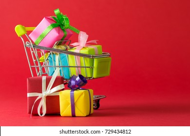 Shopping cart filled with variety color of gift boxes