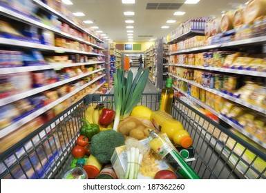 Shopping cart with foods between store shelves in a supermarket.