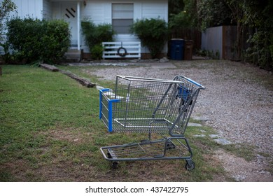A shopping cart in front of an old house in an impoverished neighborhood