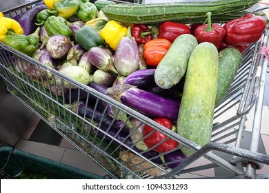 A shopping cart full with fruits and vegetables on supermarket, selective focus.