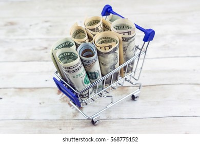 Shopping cart full of money (USD Dollar). Multi currency basket, business, finance, economy concept. Soft focus image