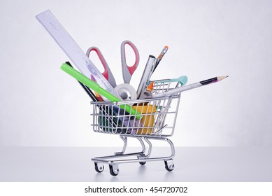 Shopping cart full of school objects: pens, markers, scissors, pencils, ruler, sharpener, paint, crayons. Conceptual.