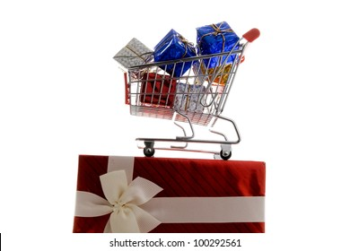 shopping cart with gift box wrapped in colored paper and ribbon on white background
