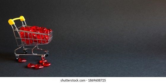 Shopping cart with glass red hearts-buying gifts for loved ones, couples in love on Valentine's day. Promotions in the holiday of lovers, products with love. Space for text, banner. Black background