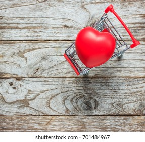 Shopping cart and heart on wood background