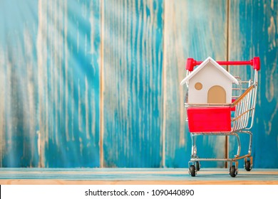Shopping cart and home model put in inside on the wood vintage blue background, Buy or sell a house and real estate for working capital concept.