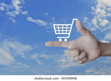 Shopping cart icon on finger over blue sky, Shop online concept