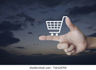 Shopping cart icon on finger over sunset sky, Shop online concept