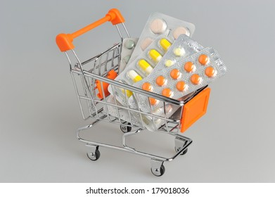 Shopping cart with medical supplies on gray background