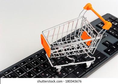Shopping cart on black keyboard on gray background