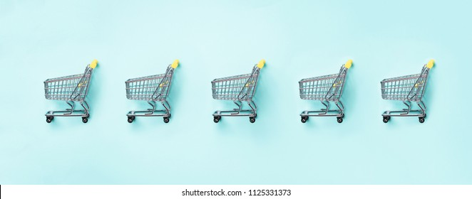 Shopping cart on blue background. Minimalism style. Creative design. Top view with copy space. Shop trolley at supermarket. Sale, discount, shopaholism concept. Consumer society trend.