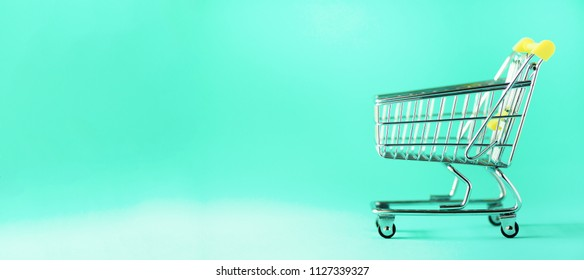 Shopping cart on blue background. Minimalism style. Creative design. Copy space. Banner. Shop trolley at supermarket. Sale, discount, shopaholism concept. Consumer society trend.