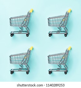Shopping cart on blue background. Minimalism style. Creative design. Top view with copy space. Shop trolley at supermarket. Sale, discount, shopaholism concept. Consumer society trend
