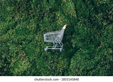 Shopping cart on green grass, moss background. Top view. Minimalism style. Creative design. Shop trolley. Sale, discount, shopaholism, ecology concept. Sustainable lifestyle, conscious consumption. - Shutterstock ID 1855145848