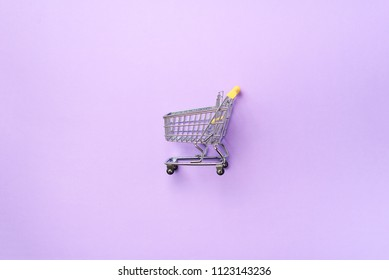 Shopping cart on purple background. Minimalism style. Creative design. Top view with copy space. Shop trolley at supermarket. Sale, discount, shopaholism concept. Consumer society trend.