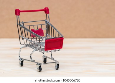 Shopping cart on wooden surface. Symbol of consumerism