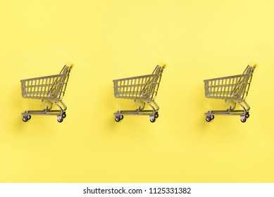 Shopping cart on yellow background. Minimalism style. Creative design. Top view with copy space. Shop trolley at supermarket. Sale, discount, shopaholism concept. Consumer society trend.