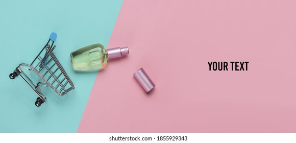 Shopping cart, perfume bottle on a blue-pink pastel background. Copy space. Top view. Minimalism