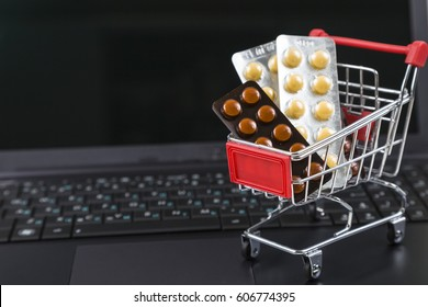 Shopping cart with pills on a laptop. Purchase of medicines online.