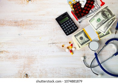 Shopping cart with pills,money and calculator on a wooden background. Paid medicine.