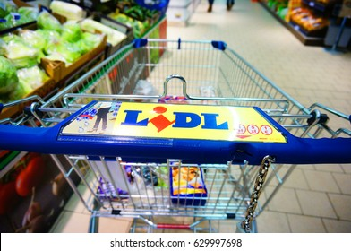 Shopping cart with products next to vegetables in a Lidl supermarket on December 2013 in Poznan, Poland