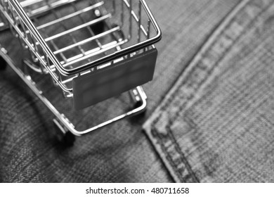 Shopping cart put on the jean pocket surface as a background represent the shopping and apparel concept related idea.