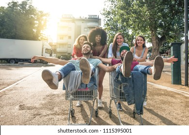 shopping cart riding race. multi ethnic young friends pushing shopping trolleys while guys sitting on carts.