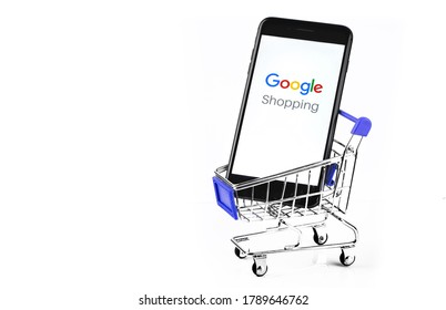 shopping cart with smartphone with Google Shopping logo on the screen. Google is the biggest Internet search engine in the world. Moscow, Russia - July 10, 2020