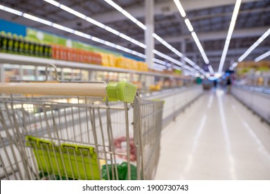 Shopping cart in super market or convenience store with shelves of frozen food