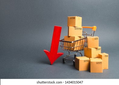 Shopping cart supermarket with boxes and a red arrow down. Falling consumer demand, declining exports or imports. The decline in production of goods and products, the economic downturn and recession.