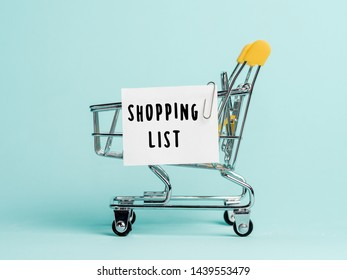 Shopping cart and text shopping list on white paper note list. Shopping list concept on blue background.
