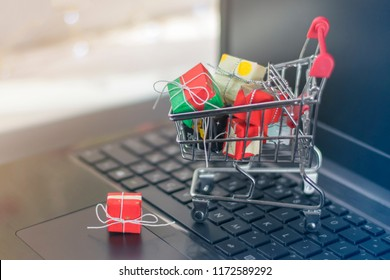 Shopping cart with a variety of gifts on the laptop keyboard. Online shopping concept.