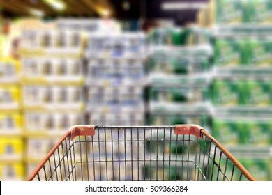 Shopping Cart View in front of can of abstract blur background of beer can on Shelf in Supermarket Background use for alcohol drink concept.
