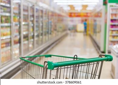 Shopping Cart view in supermarket aisle milk yogurt frozen food freezer. (lens blur effect )