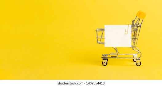 Shopping cart and white paper note list over yellow background. Shopping concept on bright yellow background. Empty white paper note over shopping cart. Copy space for text or design. Banner