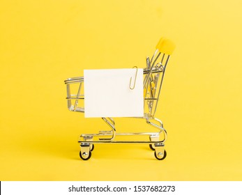 Shopping cart and white paper note list over yellow background. Shopping concept on bright yellow background. Empty white paper note over shopping cart. Copy space for text or design.
