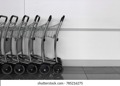 Shopping carts or luggage trolleys against refined panel wall. Abstract black and white photo of shopping mall, parking lot or airport photo with copy space.