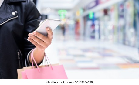 Shopping and Cashback concept, Unrecognizable woman with smartphone at mall background, panorama, copy space