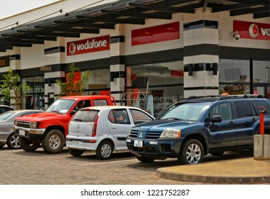 Shopping center and cars. Vodafone office. Vehicles in a parking lot. Shopping Mall. Modern urban landscape in developing countries. West Africa, Ghana, Accra – January 20, 2017