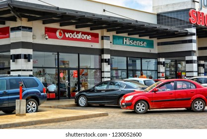 Shopping center and cars. Vodafone office. Vehicles in a parking lot. World brands. Hisense store. Shopping Mall. Modern urban landscape. Market in Ghana, Accra – January 20,1017