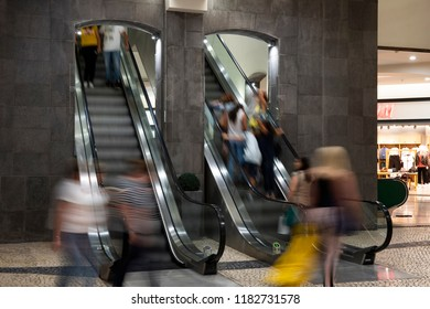 Shopping center. Escalator with buyers. Blurred motion.