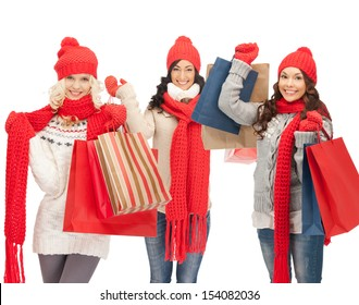 shopping and christmas concept - girls in red scarfs and hats with shopping bags