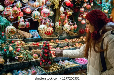 Shopping for Christmas Holidays, woman at market display window choosing Christmas tree decorations, balls and other seasonal art crafted products of modern, vintage and traditional styles