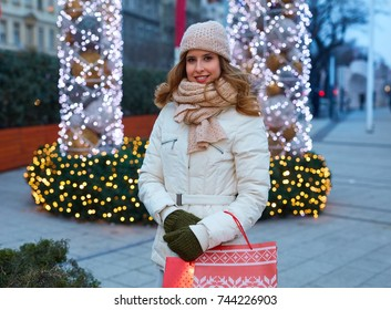 Shopping for Christmas. Young happy woman doing Christmas shopping holding christmas decorated shopping bags in front of christmas lights.