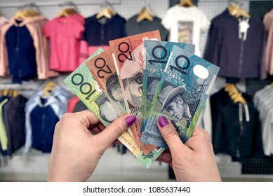 Shopping in clothes store, female hands with australian dollars