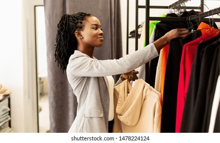 Shopping Concept. African American Lady Picking Trendy Clothes In Fashion Store.