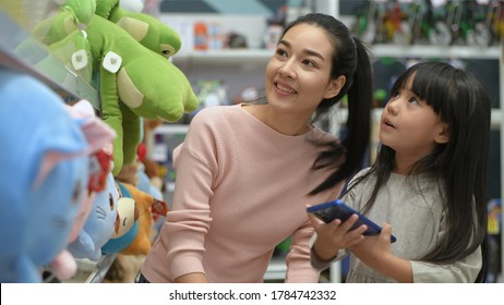 Shopping concept. Asian mother and daughter are buying dolls in the mall.