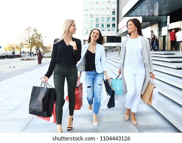 Shopping Concept - Beautiful girls with shopping bags walking at the mall
