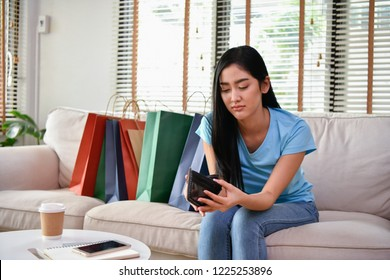shopping concept. Beautiful girls are having financial problems. Beautiful girl looking empty wallet