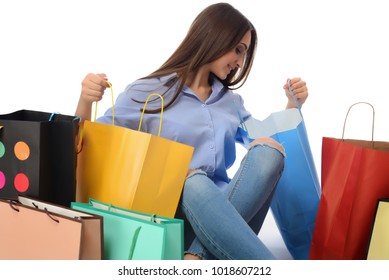 Shopping concept. Beautiful smiling brunette with shopping bags talking on the phone. isolated